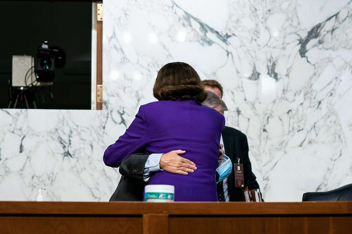 Senate Judiciary Committee Chairman Sen. Lindsey Graham, R-S.C., and Sen. Dianne Feinstein, D-Calif., hug Thursday after the end of the fourth day of committee hearings for Supreme Court nominee Amy Coney Barrett.
