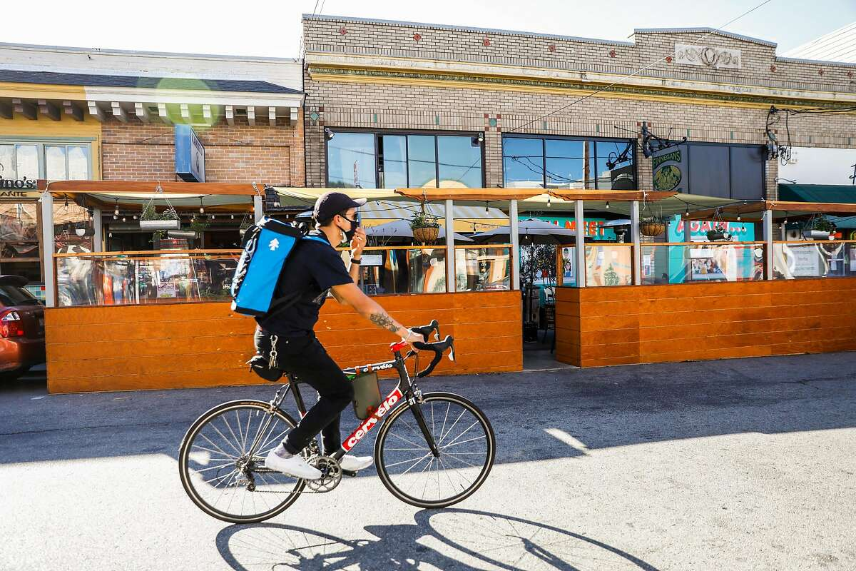 A bicyclist passes the parklet in front of Zazie.