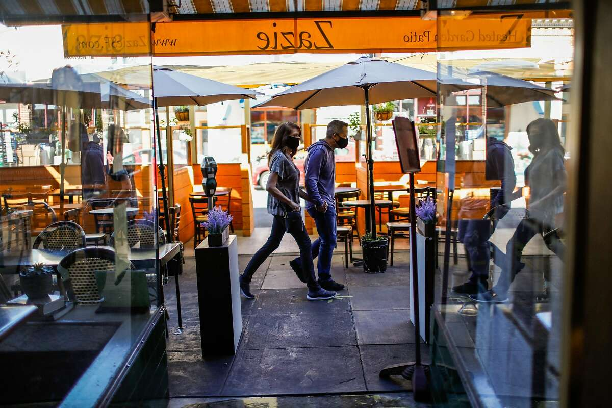 A couple walks past the parklet at Zazie restaurant in Cole Valley on Tuesday, Oct. 13, 2020 in San Francisco, California.