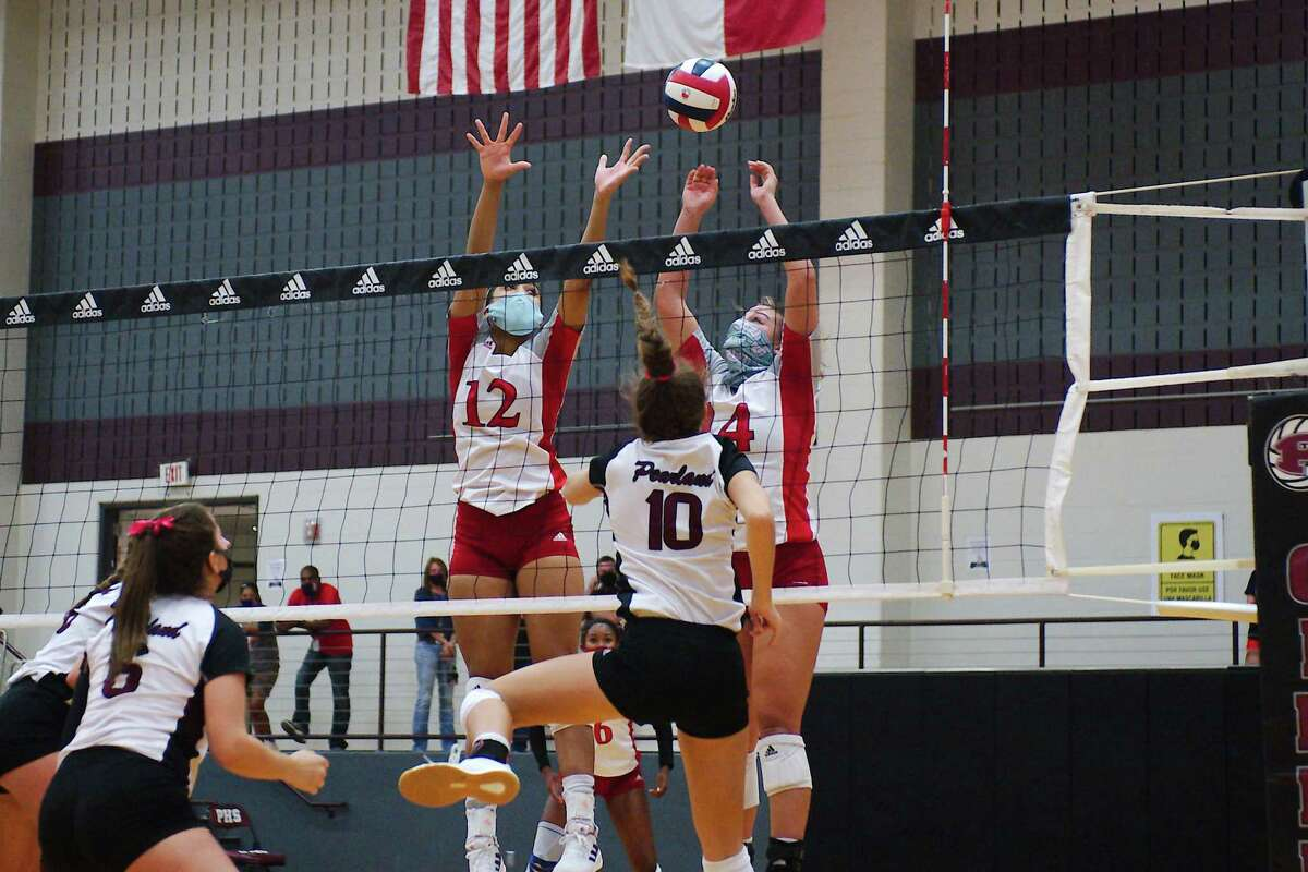 Dawson's Ava Kennon (12) and Dawson's Kylie Nance (14) go high to block a shot by Pearland's Madie Whitehead (10).