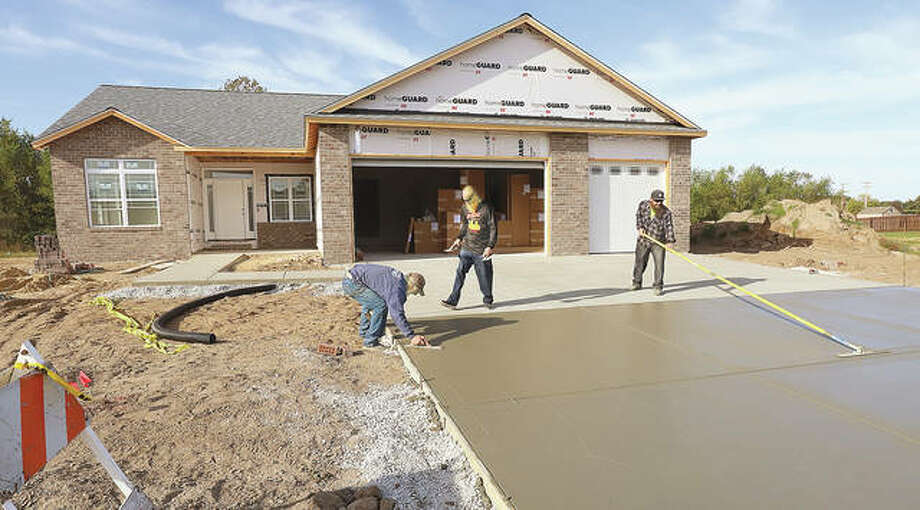 Workers spread a pour of concrete for the driveway this week at a house nearly completed in the 100 block of Shawnee Street in Wood River. Currently 19 new homes are being built in the community.