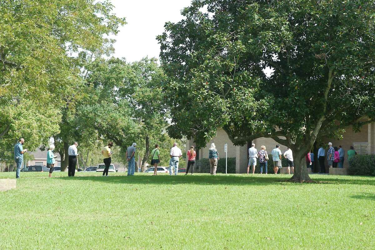 Voters string across a walk at Galveston County's North County Annex in League City as they wait to cast ballots on the first day of early voting on Tuesday, Oct. 13.