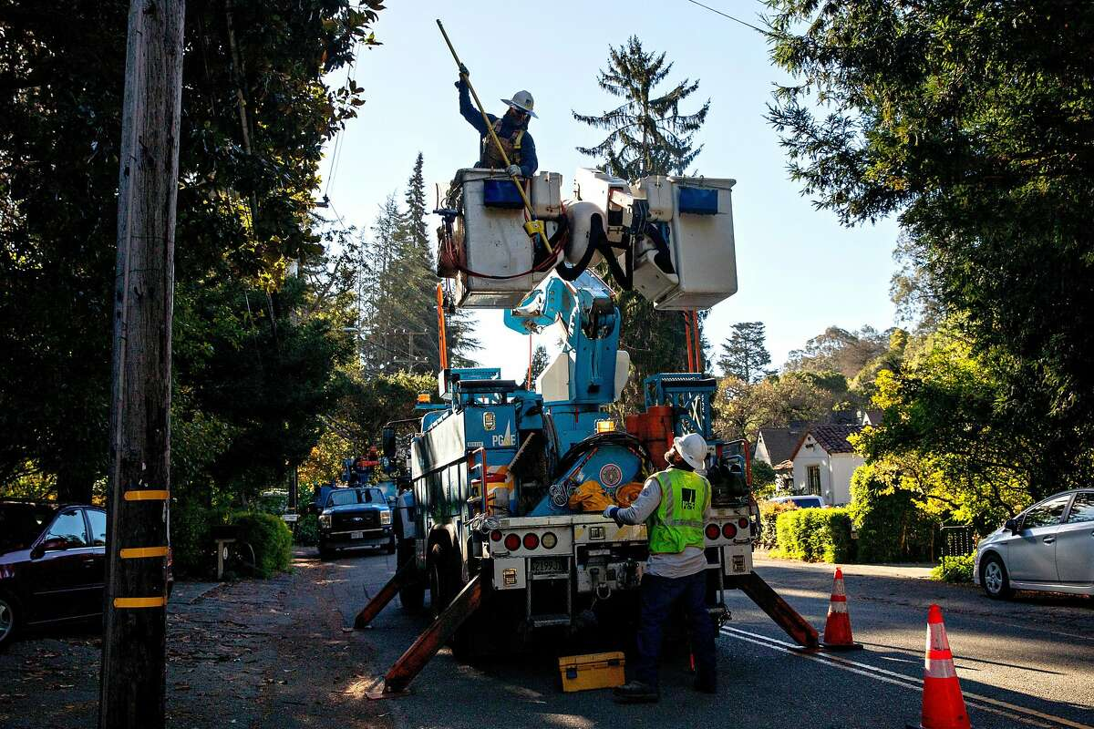 PG&E line inspector Kirk Thompson works to clear lines so crews can begin removing a tree that crashed into live power lines along Mountain Boulevard in the Montclair Village neighborhood of the Oakland hills.