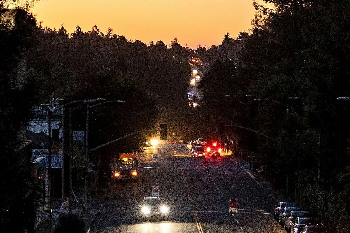 Cars drive along Mountain Boulevard in Montclair Village that was left in the dark after PG&E shut off power to the area.