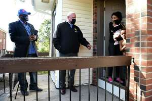 From left, the Rev.  Wayne McCrea and New Haven Assistant Police Chief Karl Jacobson speak with Diamond Short and her daughter, Jream Jones, 2 months, and son, Jurell Law, 6, at the Presidential Gardens on Dixwell Avenue in New Haven on Oct. 15, 2020, following an incident of a baby found in a dumpster at the apartment complex earlier in the week.