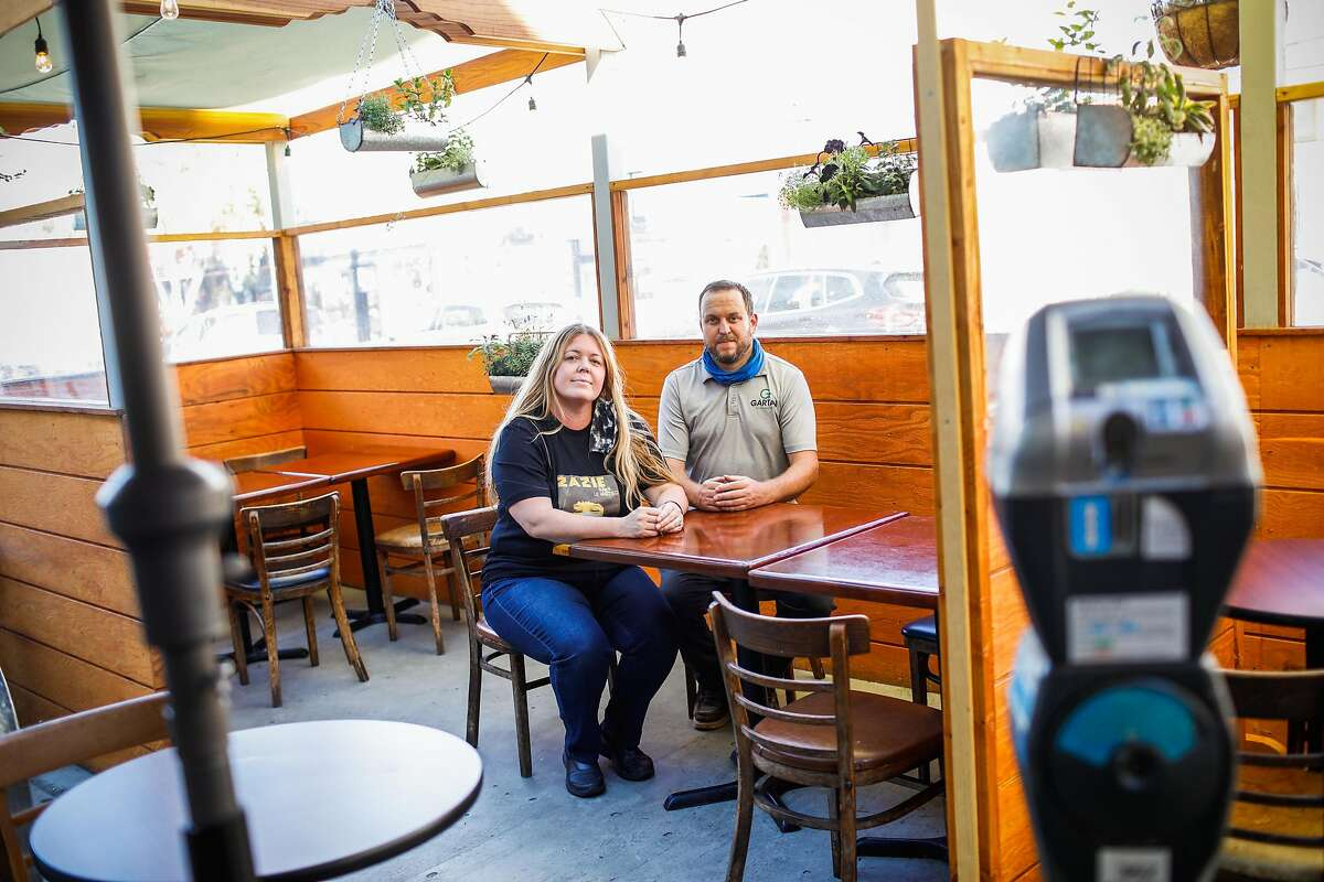Zazie co-owner Megan Cornelius sits with contractor Gavin Kelly in the parklet he built for the restaurant.