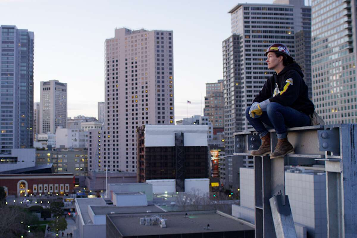 Diana Coopersmith sitting on top of one of Moscone Center West's steel beams.
