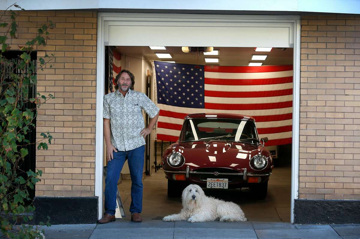 Jay Streets stands with dog Norton and his 1969 Jaguar parked in the garage at his home on Carl Street in S.F. Streets decorates the garage as a polling place for elections with red, white and blue bunting. He's decided to forgo the espresso machine this year because of the pandemic.