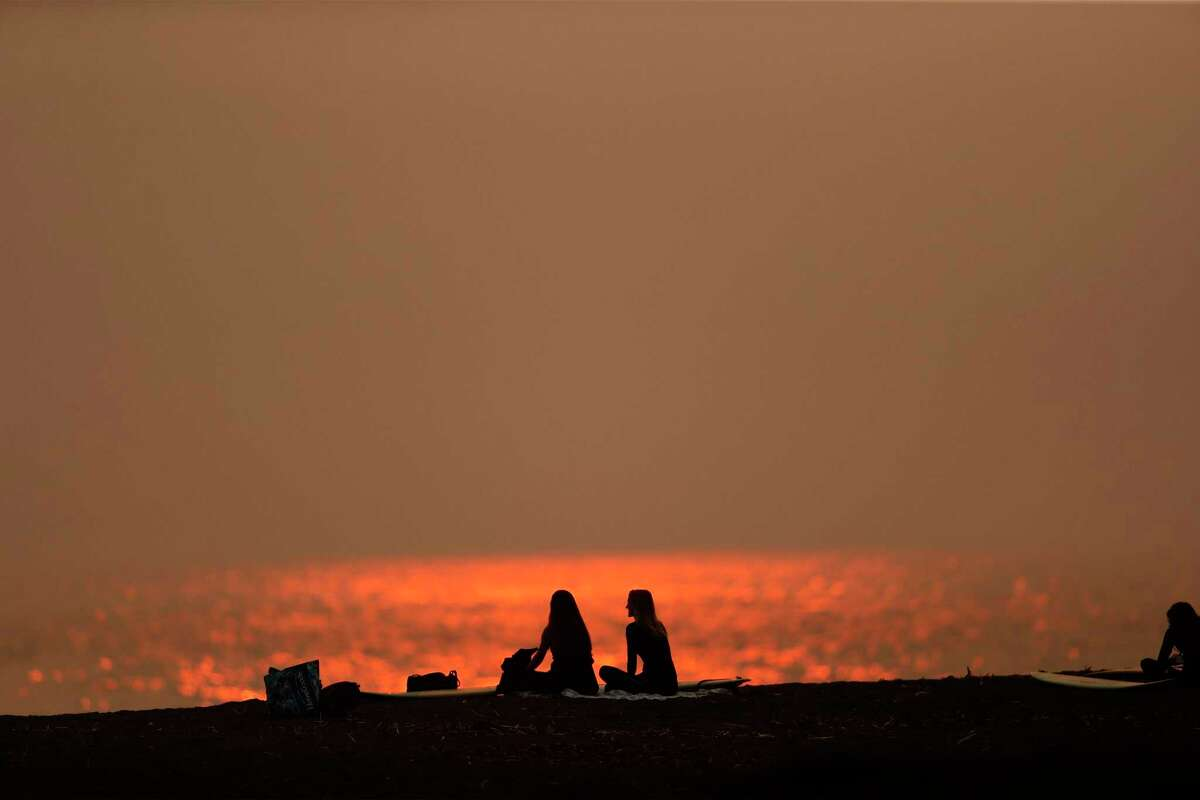 Surfers Ramsey Cook and Kristen Abberley of San Francisco rest on the beach as the sun sets at Rodeo Beach in Sausalito early this month.
