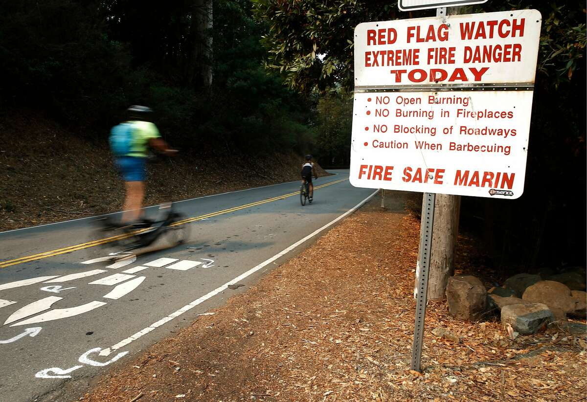 Cyclists ride on Corte Madera Avenue in Mill Valley last month as smoke from the Glass Fire in Napa and Sonoma counties blanketed the region.