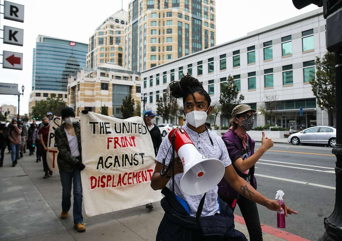 Dayton Andrews, with The United Front Against Displacement, leads a group of demonstrators along 14th St. during a protest against the City of Oakland's proposed encampment management policy in Oakland, Calif., on Saturday, October 10, 2020.