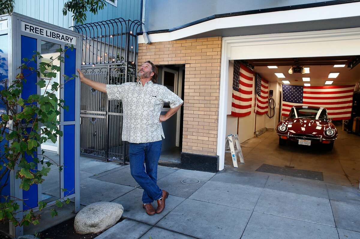 Jay Streets stands at the free library he maintains in front of his S.F. home while readying the garage as a polling place for the Nov. 3 general election.