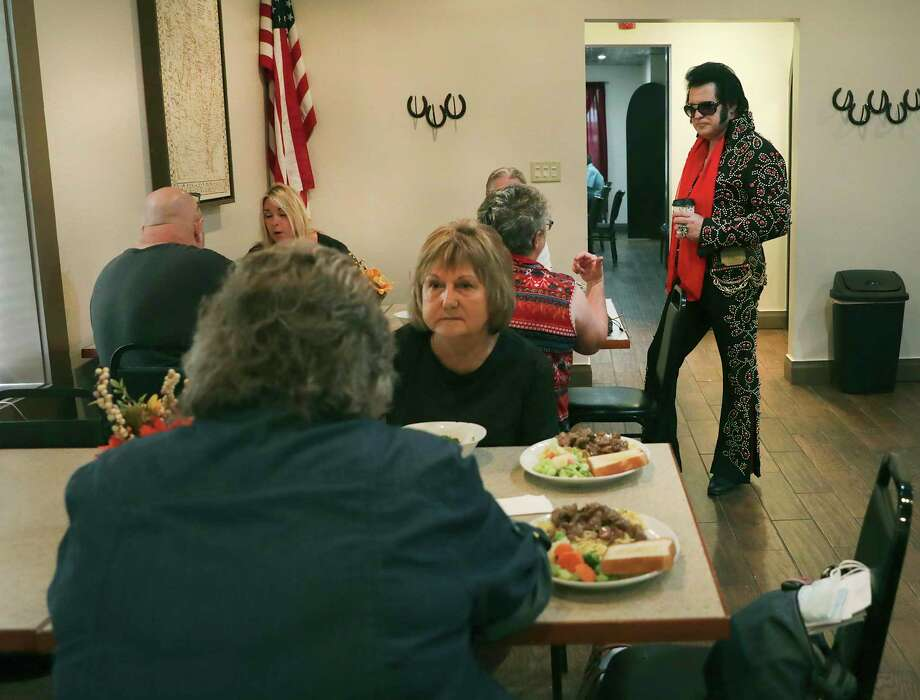 Michael McMullen, right, AKA Elvis, stops to visit with visitors in the Alcalde Hotel Dinning Hall. The historical Alcalde Hotel, where Bonnie and Clyde, and Elvis stayed at one point, has reopened as the first historical franchise for budget hotel chain OYO, in Gonzales, Texas, on Thursday, Oct. 15, 2020. Photo: Bob Owen, Staff-photographer / San Antonio Express-News / ©2020 San Antonio Express-News