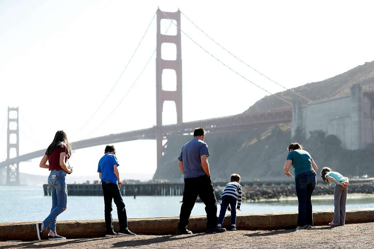The Edwards' family from Phoenix, Arizona, look at crabs along the shoreline as they enjoy the relatively cool temperatures near the Golden Gate Bridge in Sausalito, Calif., on Thursday, October 15, 2020.