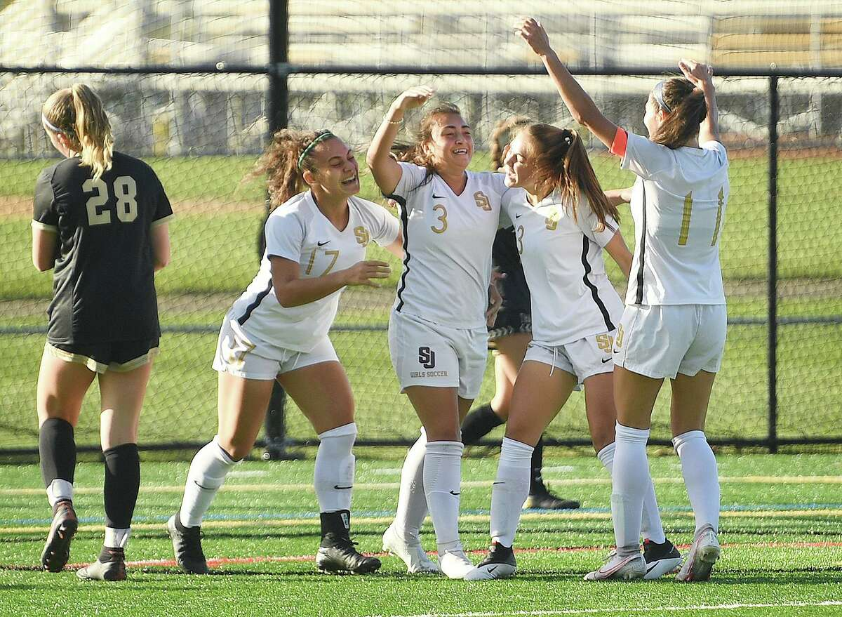 St. Joseph teammates celebrate a first half goal by Andriana Cabral, center, during their girls soccer match at rival Trumbull High School in Trumbull, Conn. on Thursday, October 15, 2020.