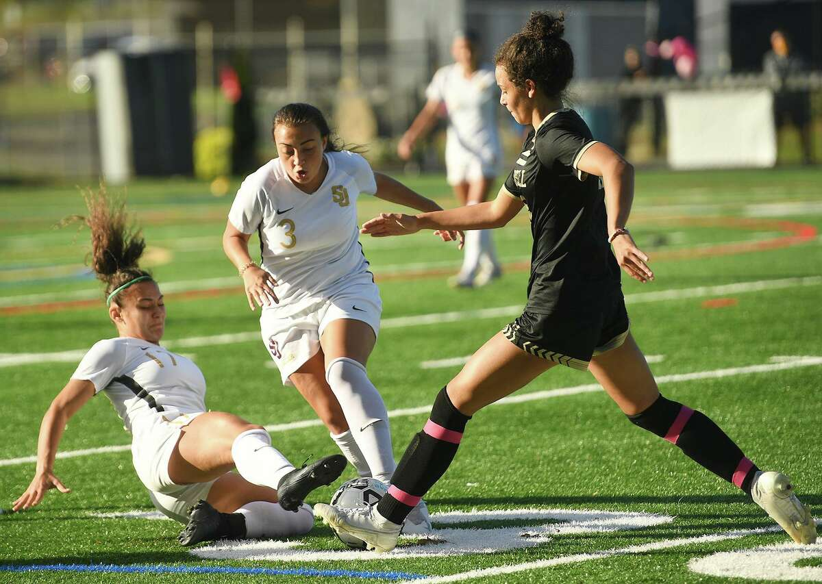 From left; St. Joseph's Anastasia Kydes and Andriana Cabral converge on the ball with Trumbull's Sophia Lowenberg during the first half of their girls soccer match at Trumbull High School in Trumbull, Conn. on Thursday, October 15, 2020.
