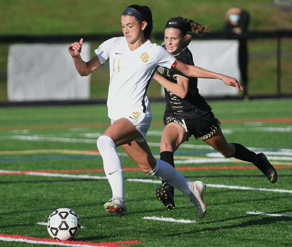 St. Joseph's Maddie Fried races in toward goal ahead of Trumbull defender Megan Garrity during their girls soccer match at Trumbull High School in Trumbull, Conn. on Thursday, October 15, 2020.