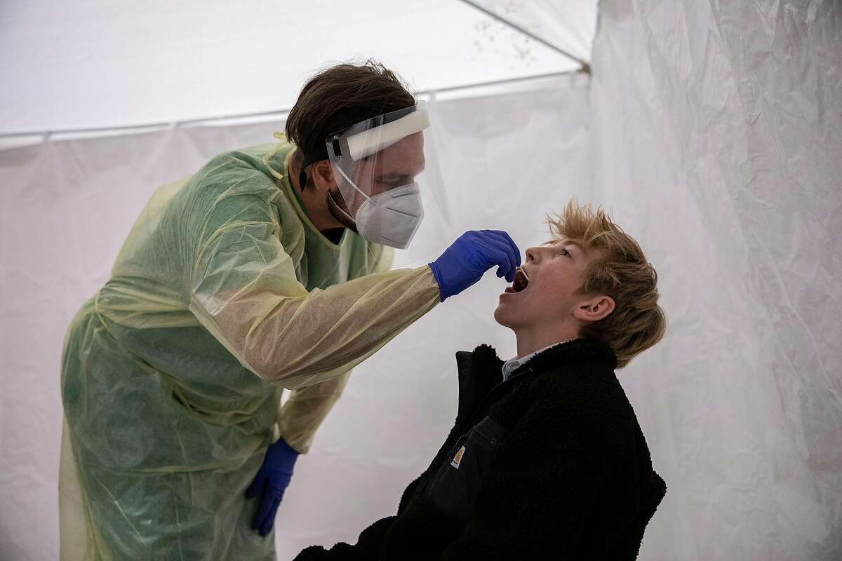 A member of the German Red Cross takes a throat swab at a coronavirus testing station in Berlin.