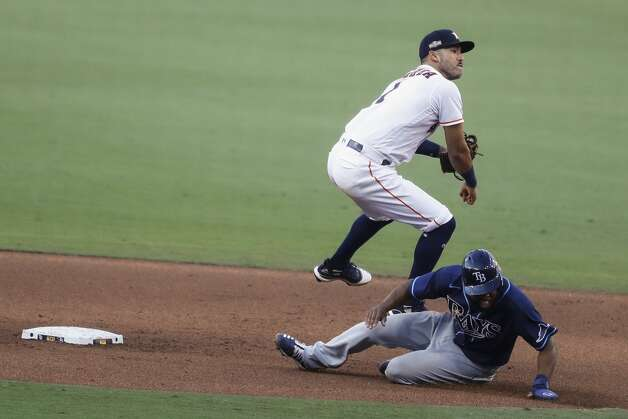 Houston Astros Carlos Correa (1) leaps over Tampa Bay Rays Manuel Margot as he turns a double play on a grounder by Joey Wendle during the eighth inning of Game 5 of the American League Championship Series at Petco Park Thursday, Oct. 15, 2020, in San Diego. Photo: Karen Warren/Staff Photographer / © 2020 Houston Chronicle