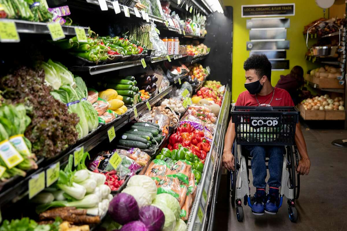 Garnett Silver-Hall, 19, shops for fresh organic groceries at the Food Conspiracy Co-op in Tucson, Ariz.