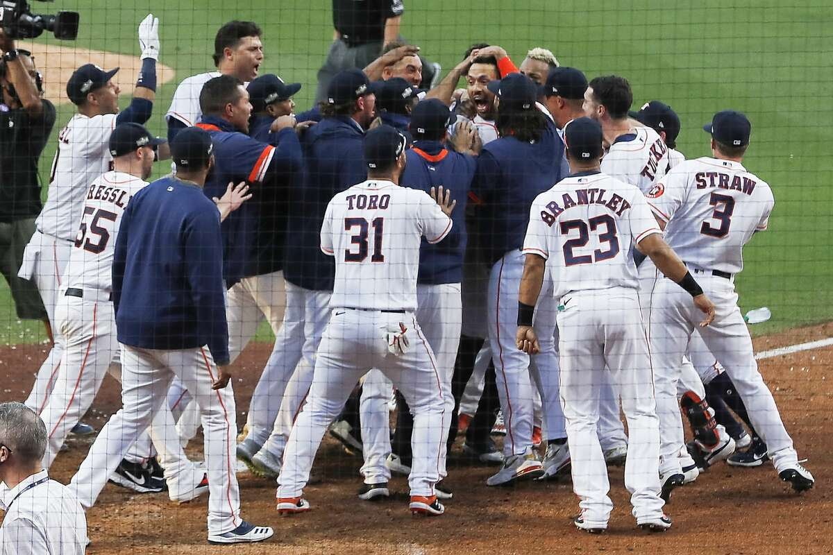 The Houston Astros surround Carlos Correa as the celebrated after his walk off home run to win 4-3 against the Tampa Bay Rays during Game 5 of the American League Championship Series at Petco Park, Thursday, October 15, 2020, in San Diego.