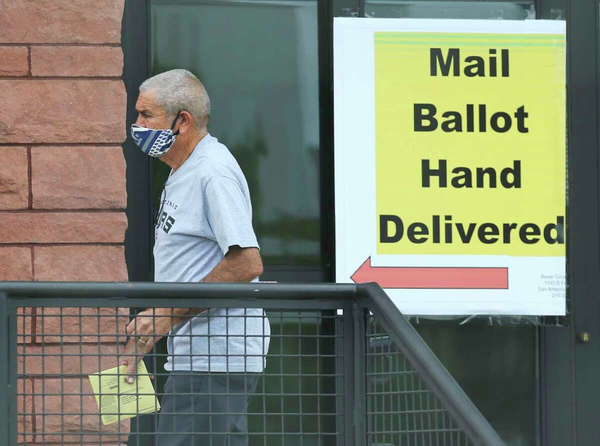 A voter hand delivers his mail ballot at the Bexar County Elections headquarters on Thursday, Oct. 15, 2020. At the same time, at the other end of the building, voters were waiting in line to cast their votes during the third day of early voting.
