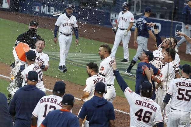Houston Astros Alex Bregman and Yuli Gurriel (10) dump an ice bucket on Carlos Correa as they celebrate Correa's walk off home run off Tampa Bay Rays reliever Nick Anderson to win Game 5 of the American League Championship Series 4-3 at Petco Park Thursday, Oct. 15, 2020, in San Diego. Photo: Karen Warren/Staff Photographer / © 2020 Houston Chronicle