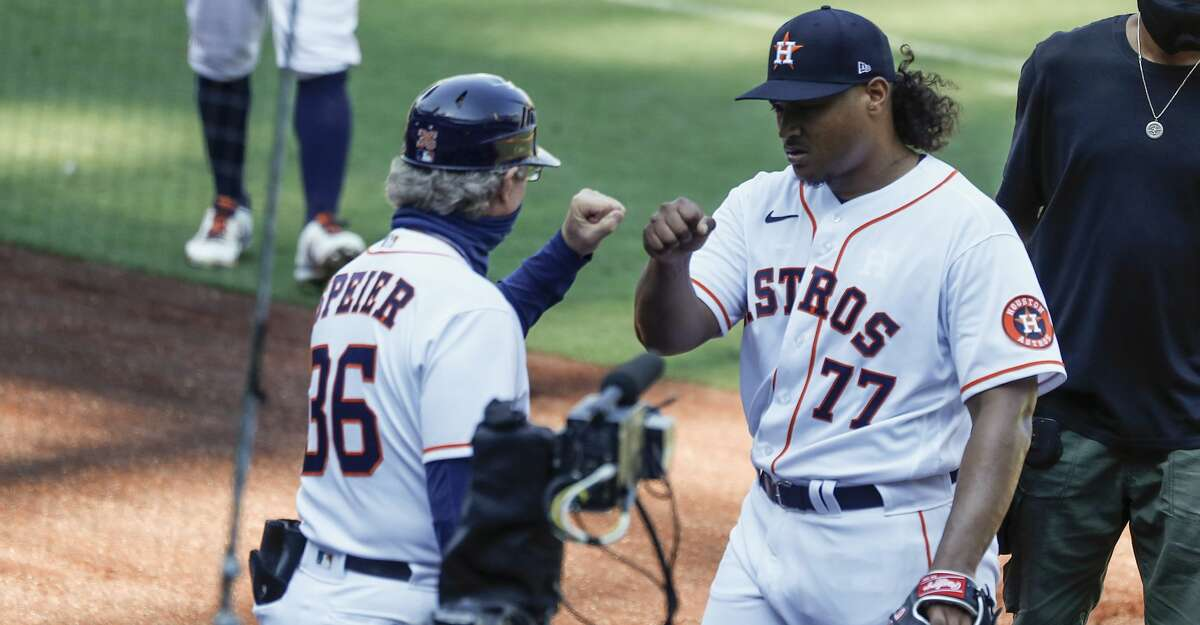 Houston Astros first base coach Chris Speier, left fist bumps starting pitcher Luis Garcia (77) as he comes off the field after the first inning of Game 5 of the American League Championship Series against the Tampa Bay Rays at Petco Park Thursday, Oct. 15, 2020, in San Diego.