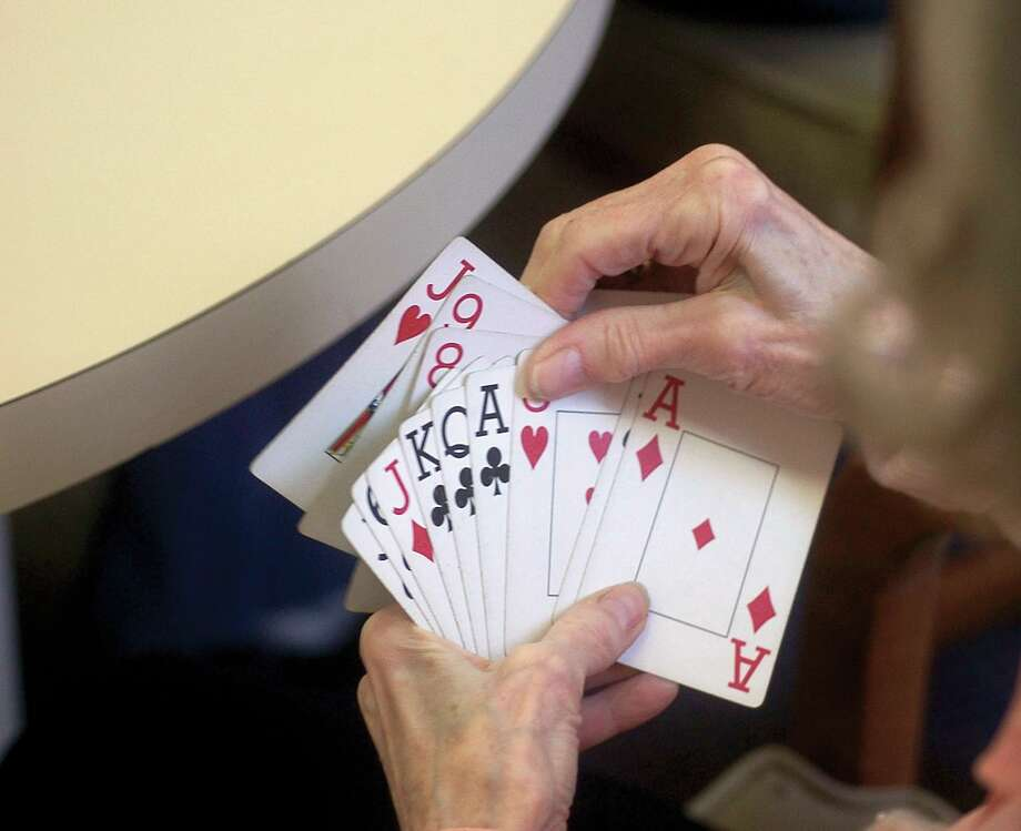 A player holds her cards during a bridge game on Jan. 19, 2005, at the Greenwich Senior Center. Photo: File / Helen Neafsey / Hearst Connecticut Media