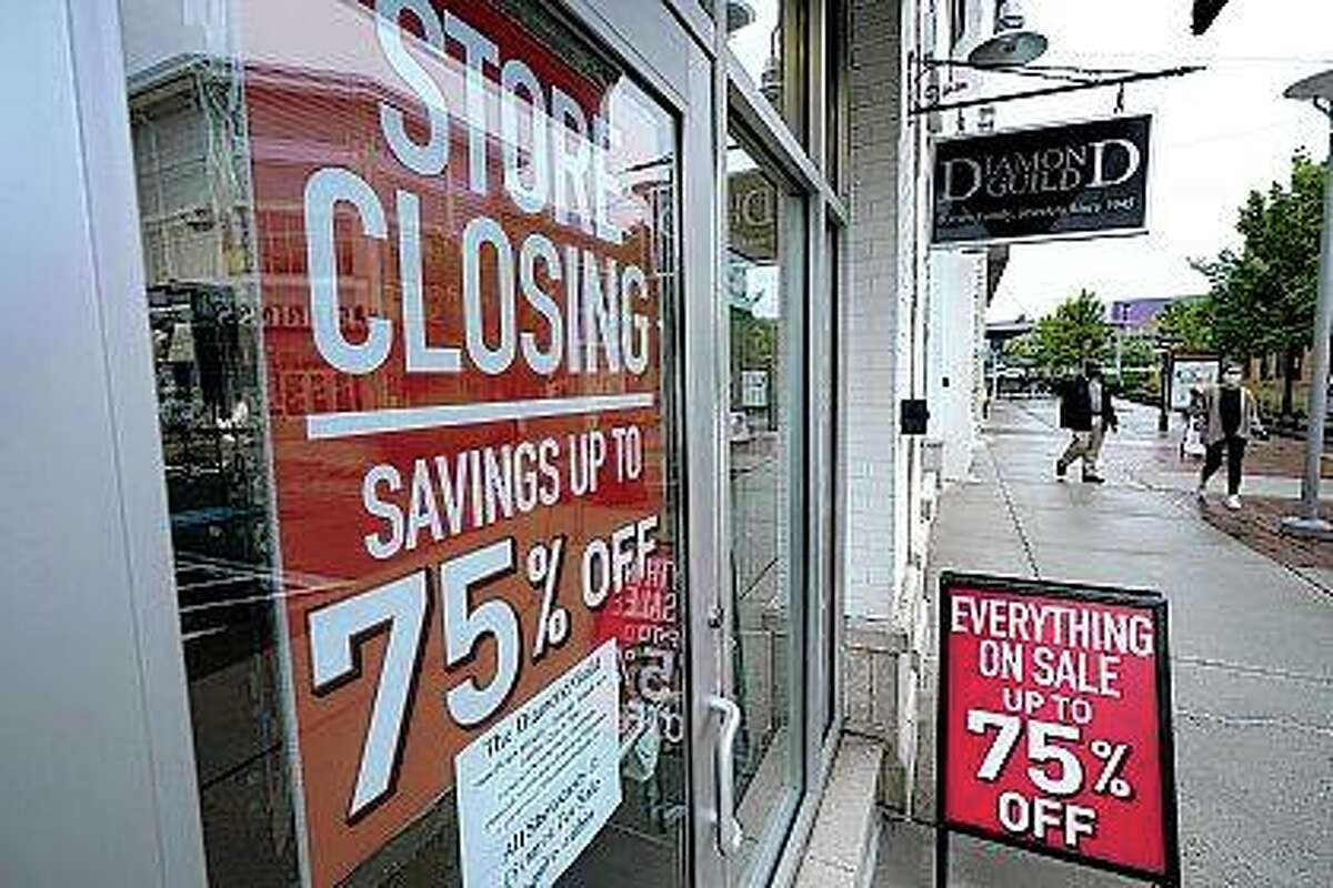 Pedestrians walk past a business storefront with store closing and sale signs in September in Dedham, Massachusetts. U.S. employers advertised for slightly fewer jobs in August while their hiring ticked up modestly.