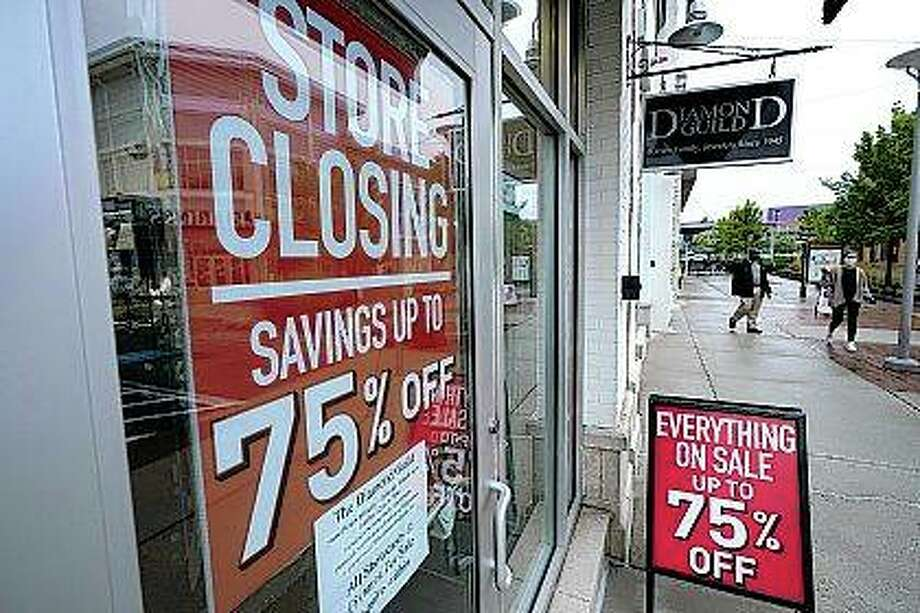 Pedestrians walk past a business storefront with store closing and sale signs in September in Dedham, Massachusetts. U.S. employers advertised for slightly fewer jobs in August while their hiring ticked up modestly. Photo: Steven Senne | Associated Press