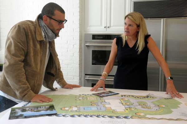 Real Estate Broker Steve Gold and Realtor Tara Hawley look over ground plans in the kitchen of 115 Senate Lane, in Fairfield, Conn. Oct. 15, 2020.