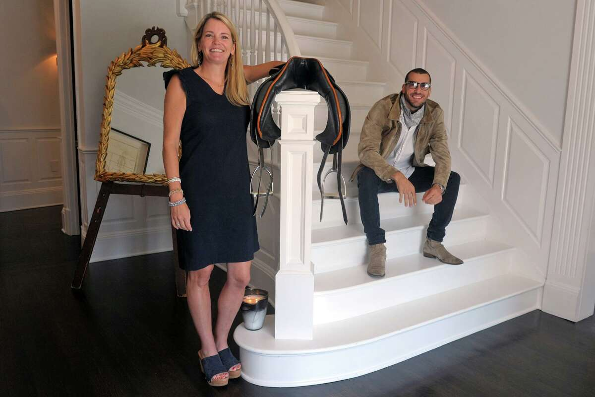 Realtor Tara Hawley and Real Estate Broker Steve Gold pose in the foyer of 115 Senate Lane, in Fairfield, Conn. Oct. 15, 2020. He is the co-listing agent for this house, along with Tara Rowe Hawley. On Oct. 15, he posted an Instagram story of himself driving up to the Fairfield mansion and a walk through of the home, which features quirky decor and memorabilia.