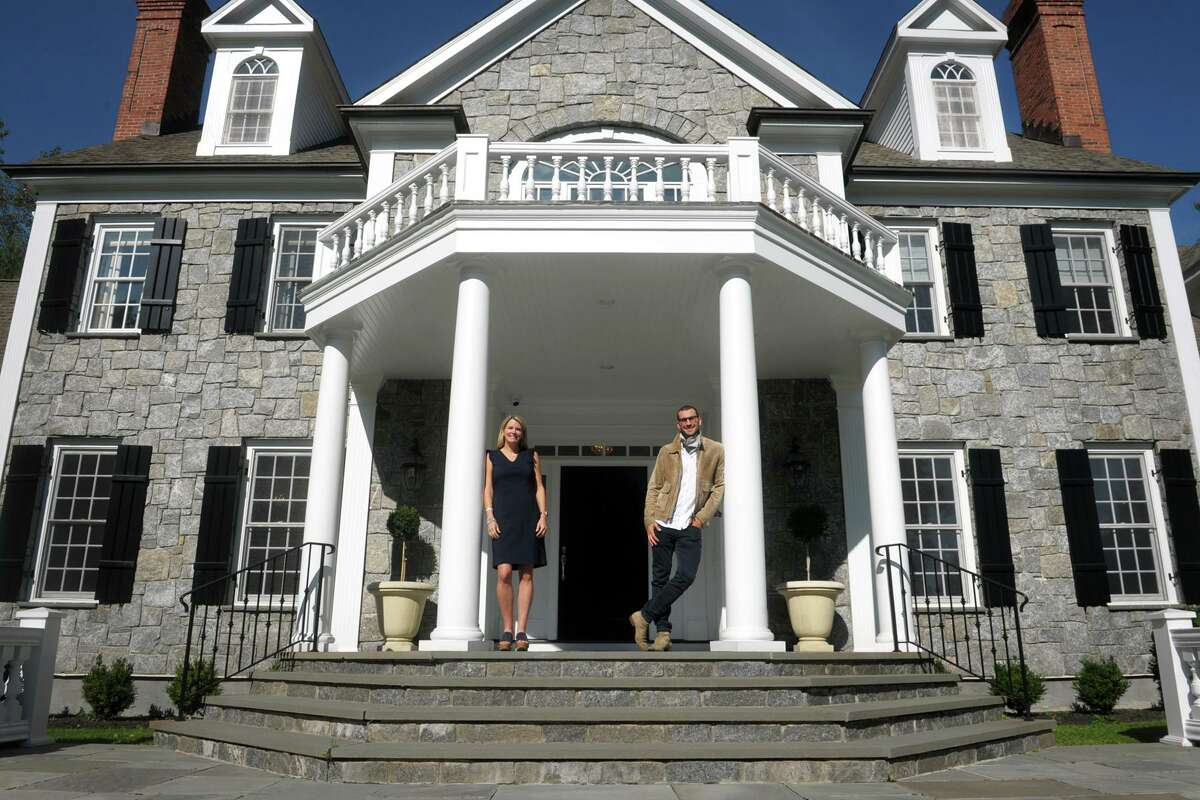 Realtor Tara Hawley and Real Estate Broker Steve Gold pose in front of 115 Senate Lane, in Fairfield, Conn. Oct. 15, 2020.