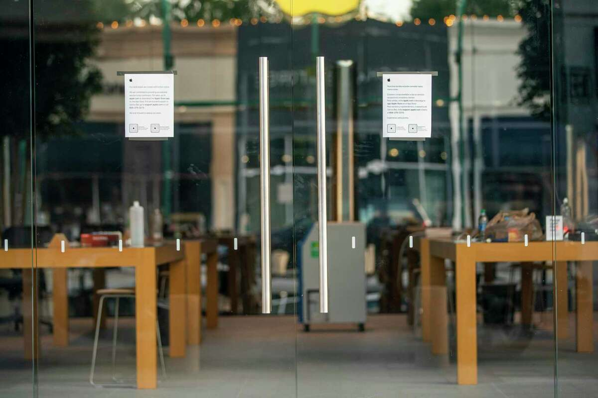 Signs on the door say that the Apple Store in Highland Village is closed, Thursday, July 9, 2020, in Houston.