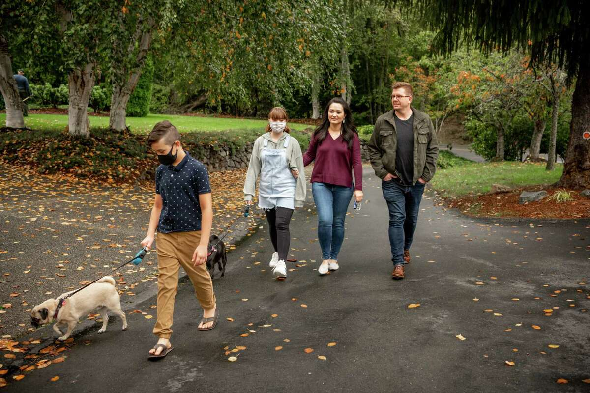 The Anderson family recently moved from San Jose to Gig Harbor, Wash., a small town about an hour from Seattle. From left: Casey, 11; Adrienne, 13; Cindy, 39; and Scott, 42, walk their dogs in their new cul de sac.