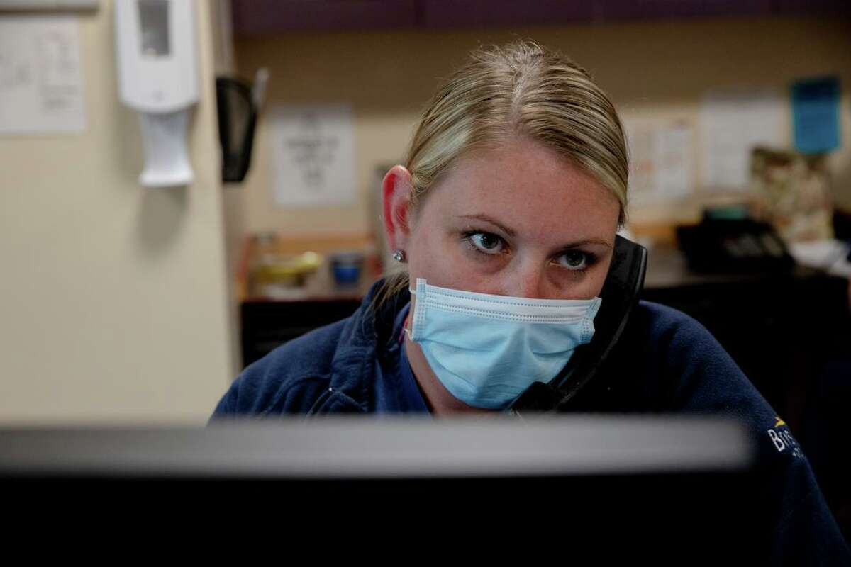 Kristin Levine, a registered nurse, talks to a patient on the phone on Thursday, Oct. 1 at Bristol Hospital. Proponents of the health information system that involved medical practitioners can share say it could have saved more lives and helped prevent health worker burnout during the first seven months of the pandemic.
