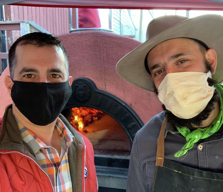 Sal Bagliavio and Frank Candullo, Bailey's Backyard masked pizza duo, in front of the restaurant's new mobile pizza oven. Photo: Contributed / Bailey's Backyard