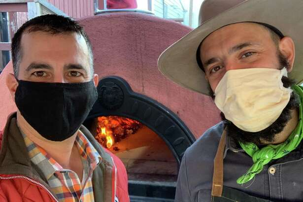 Sal Bagliavio and Frank Candullo, Bailey's Backyard masked pizza duo, in front of the restaurant's new mobile pizza oven.