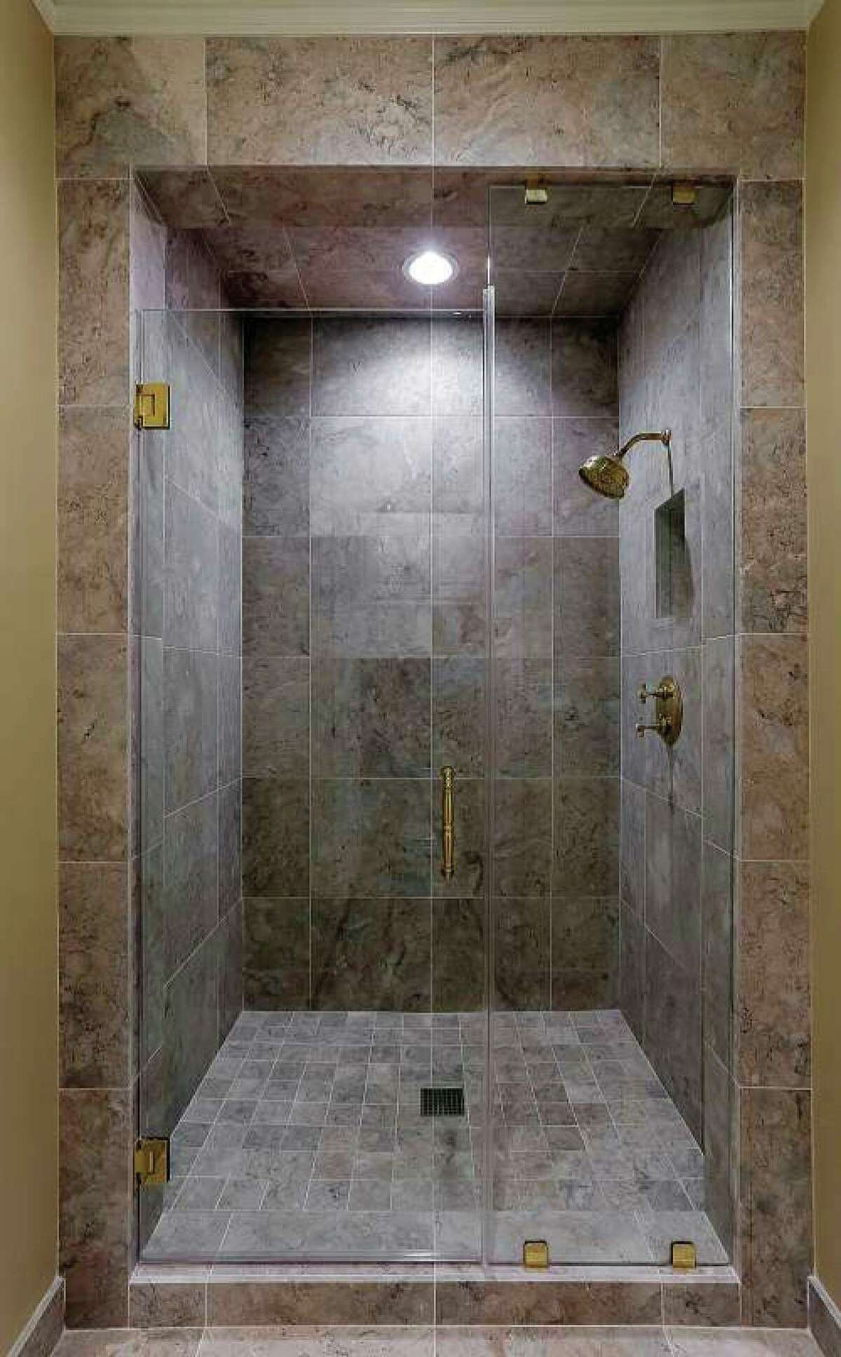 This is a frameless glass shower enclosure in neutral colors. / Courtesy of Craftsmanship By John