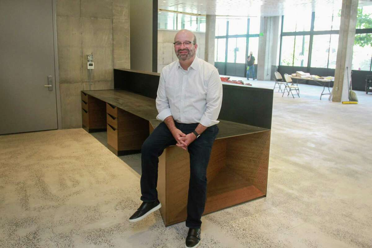 Rusty Bienvenue, executive director of both the AIA Houston and the Architecture Center Houston, poses at the reception desk in the newly renovated center, which is home to AIA Houston. Renovations on the site -- a historic downtown building -- were nearly complete in 2017 when Hurricane Harvey flooded it. They had to start completely over, including installing more flood mitigation.