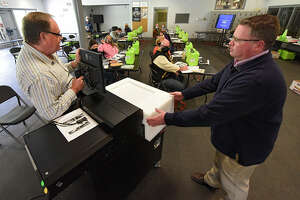 Democratic Elections Commissioner Edward McDonough, left, and Republican Elections Commissioner Jason Schofield, right, train poll workers how to set up the voting machine in preparation for the general election at Knickerbocker Ice Arena on Tuesday, Oct. 6, 2020 in Troy, N.Y. (Lori Van Buren/Times Union)