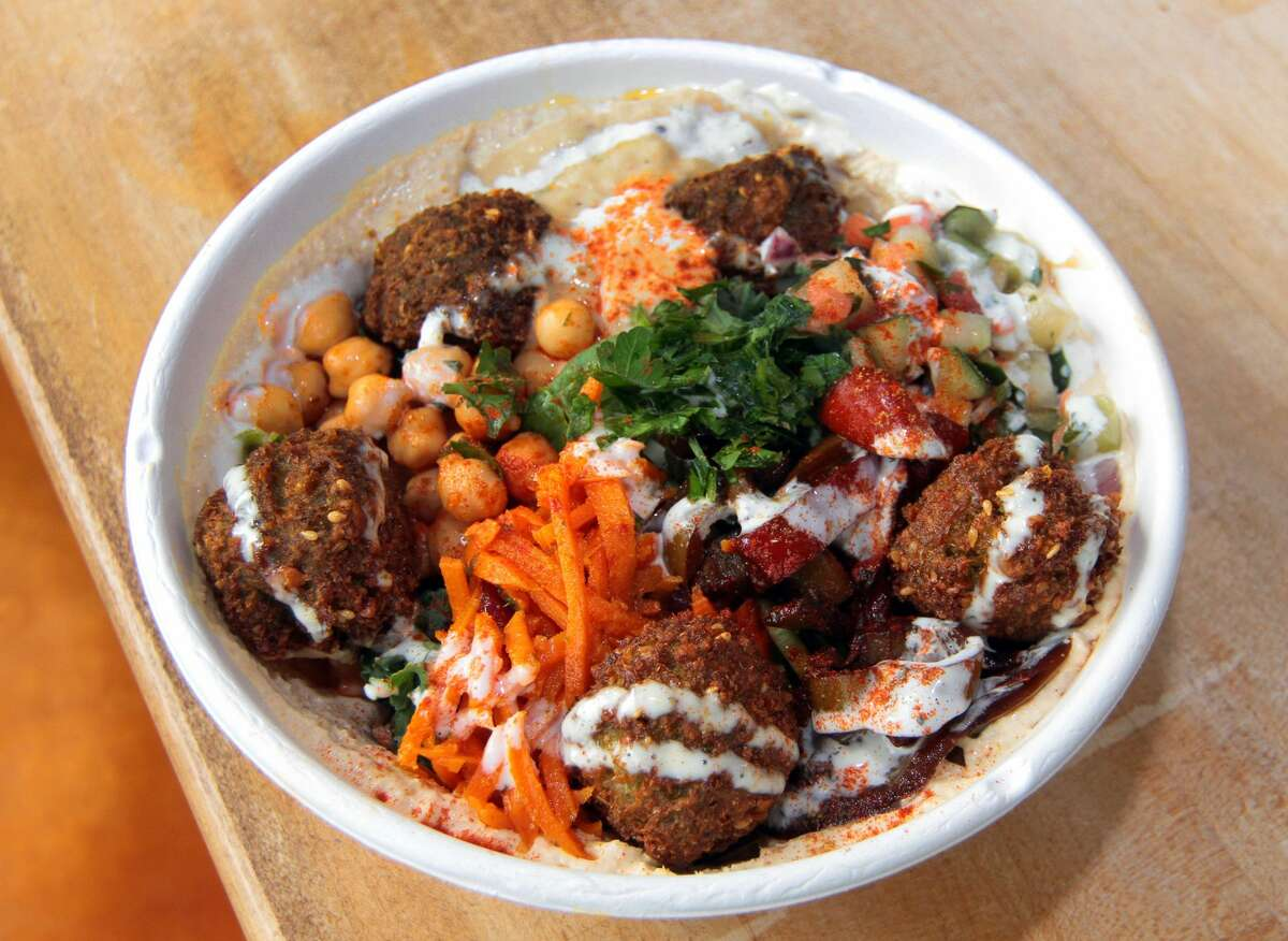 Yalla Organic Hummus & Grill in Fairfield, Conn., on Wednesday Sept. 2, 2020. This dish features salad with Magic hummus, yalla falafel, Baba Ganoush, moroccan carrots salad, chickpea salad, israeli salad, roasted red peppers salad, topped with lime garlic sauce and parsley. The story Marcia Calisman, a health coach, her husband, chef Ronen Yur, and their son, Idan Mitchel, opened Yalla in 2018. The restaurant features built-to-order bowls, wraps, pita and salads. Customers choose their hummus - options include traditional as well as a turmeric-carrot variety - a protein and toppings. For proteins, there are multiple falafel offerings, chicken shawarma, shakshuka and more. Toppings include tabbouleh, Israeli and beet salad and baba ghanoush. Mitchel says the build-your-own style is inspired by his mother's experience as a health coach and allows the restaurant to cater to any dietary need.