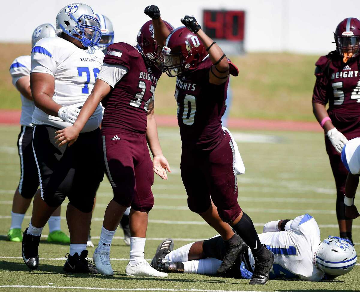 Heights defensive lineman Darius Cleveland (40) celebrates his sack of Westbury quarterback Jeremiah Randolph, bottom right, during the second half of a high school football game, Saturday, Oct. 10, 2020, in Houston.