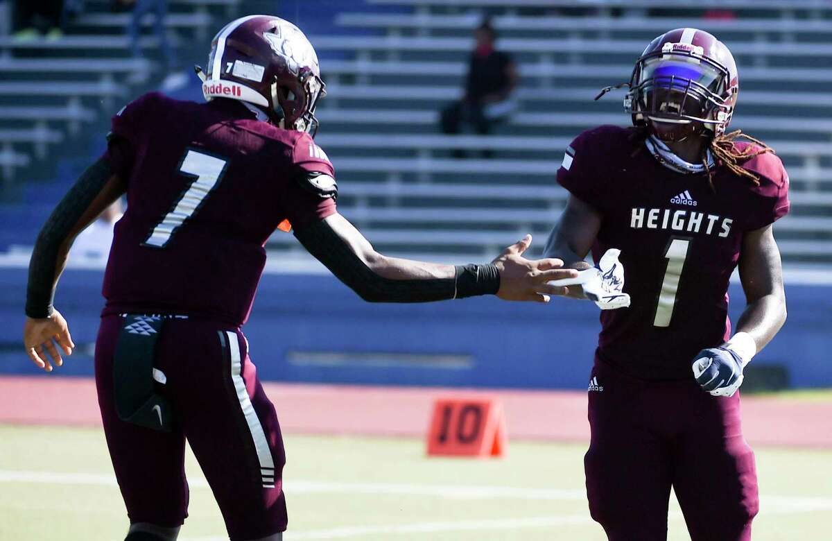 Heights running back Kendric Rhymes (1) celebrates his touchdown with quarterback Jalen Morrison during the first half of a high school football game against Westbury, Saturday, Oct. 10, 2020, in Houston.