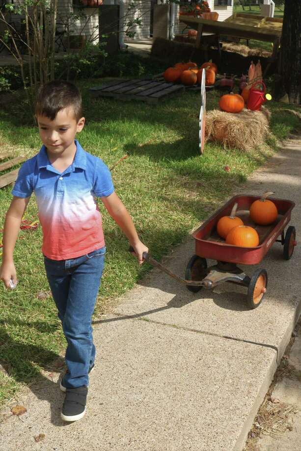 Adam Mendoza heads for the family car with some pumpkins that were just bought at the Blue Monkey Resale Shop Pumpkin Patch. Photo: Robert Avery