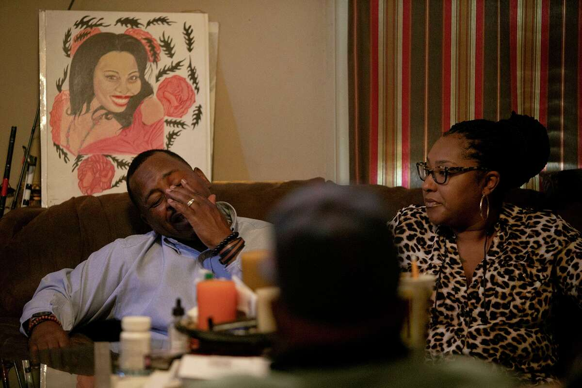 Walter Perry, left, with his wife, Alicia Perry, covers his face while his uncle, Eddie Wilson Sr., talks about his son, Eric Wilson, being arrested and beaten. Because of the arrest, the federal officials sent Eric back to prison for 21 months after they said he violated the terms of his parole for an earlier, unrelated federal conviction.