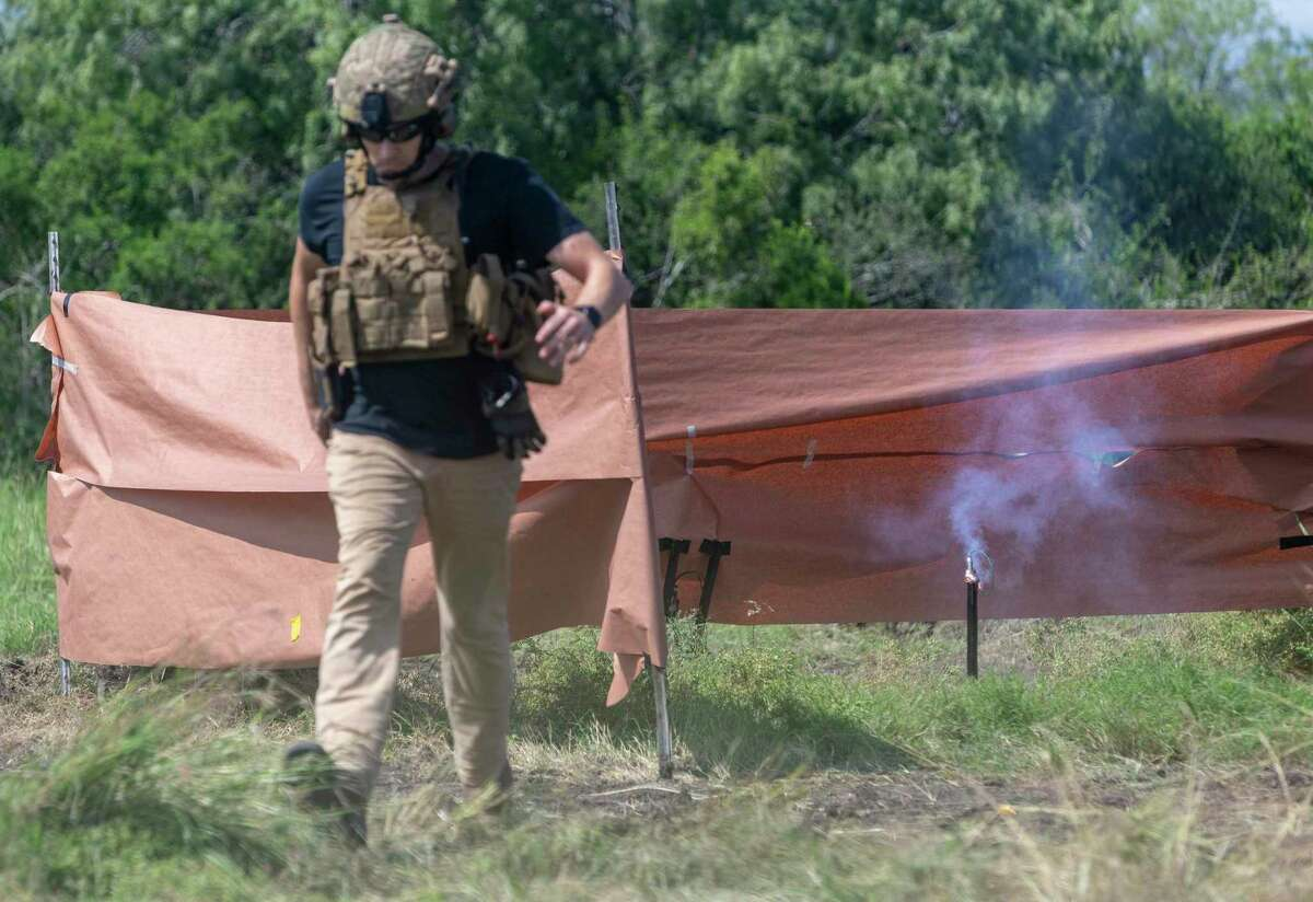 Texas Machine Gun & Ordnance's Sean Lindley runs for shelter Sept. 24, 2020 after lighting the fuse on a so-called cricket bomb while filming an Ordnance Lab Youtube channel video near George West.