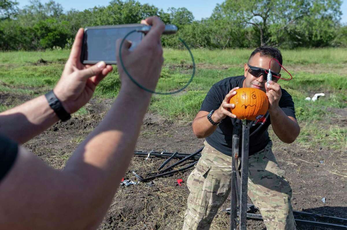 Jake Lambuth of Texas Machine Gun & Ordnance poses Sept. 24, 2020 with a cricket bomb before detonating it inside a pumpkin while filming an Ordnance Lab Youtube channel video.