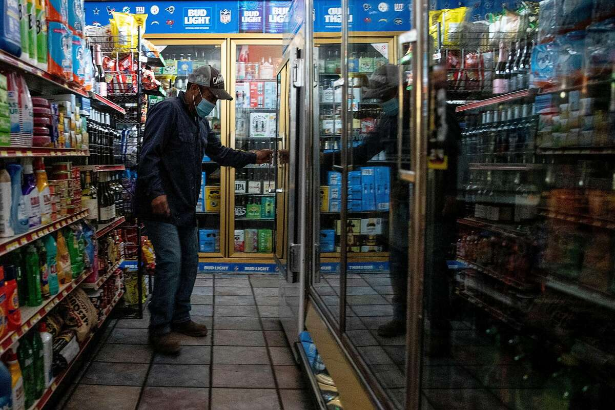A customer looks for ice in a dark freezer with no luck during a fire-prevention power outage at a Calistoga shop. More outages are expected Sunday across a widespread part of PG&E's service territory.